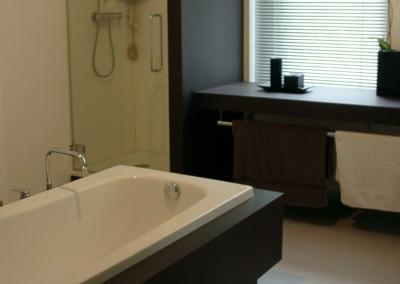 Douchewand met glasdeur, aangezette wastafel met doorlopende poot. Materiaal: watervast MDF met HPL met echt wengé houtfineer