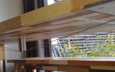 Eiken tafel, donkergekleurd, Contrasthout: dark mixed wood. Geen dikke ondersteuningsbalk, maar spandraden die doorbuigen voorkomen.
