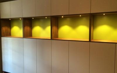 Wandvullende kast, gemelamineerde plaat, vakken: notenfineer, achterwand: lime-groen gemelamineerd