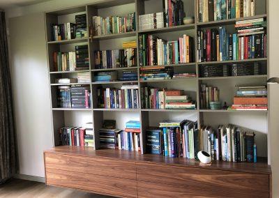 Zwevende boekenkast, materiaal gemelamineerde plaat met notenfineer,  naast open boekenkast links een afgesloten kast hier afgebeeld met de deur gesloten