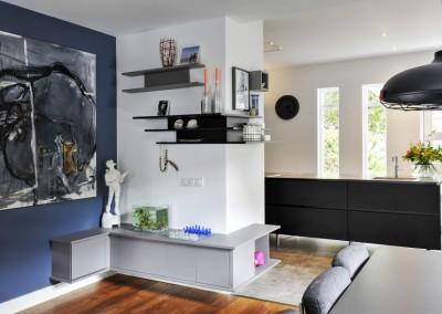 Compositie van kasten, op de achtergrond keuken, mat zwart met blad van geroest staal