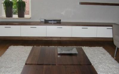 Lage salontafels, massief notenhout, poten: RVS ingefreesd; op de achtergrond hangend dressoir.