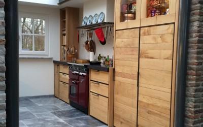 Keuken in massief eiken uitgevoerd, fronten onderkasten: ruwe eiken planken, gevat in stalen hoekprofielframe, handgrepen aangelast