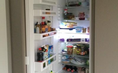 Op maat gemaakte wand met koelkast en voorraadkast en deur naar bijkeuken