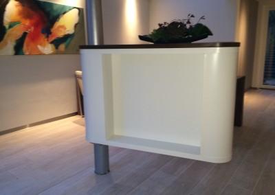 Draaibaar TV-meubel, met rondlopende schuifdeur. Deur is glad en in kleur gespoten. Ter plekke om een steunpilaar heen gebouwd+ kast is 270 graden draaibaar, zodat van meerdere kanten televisie gekeken kan worden
