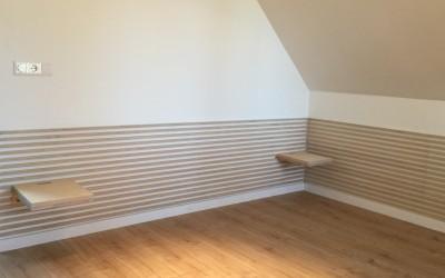Achterwand bed met schappen met gleuf voor doorvoer stekker, lambrisering loopt door gehele kamer inclusief ladekasten, ontwerp STIJLAPART