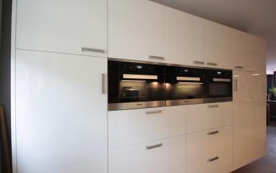 Op maat gemaakte keuken. Apparatenkast: deuren 22 mm dik, hoogglans gespoten; laden: 2 x 90 cm. breed, 3 apparaten erboven van elk 60 cm. breed