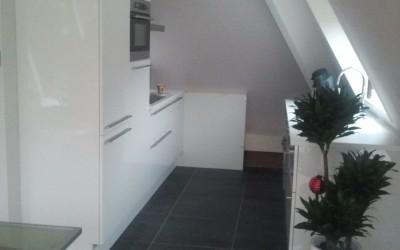 Hoogglans gespoten keuken in pyramide woning met schuine wanden, maatwerk