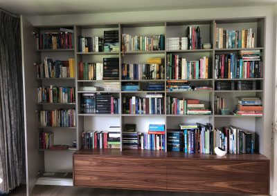 Zwevende boekenkast, materiaal gemelamineerde plaat met notenfineer, naast open boekenkast links een afgesloten kast hier afgebeeld met de deur geopend