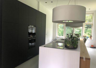 Keukenblok en apparatenkast gemaakt van Fenix materiaal, dit is supermat, krasvast en vlekvrij, boven keukenblok afzuigkap met hetzelfde uiterlijk als de lampen