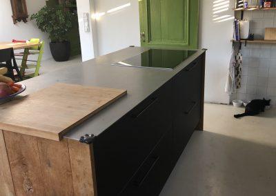 Keuken, kookeiland, materiaal laden: mat zwart fenix (vingerafdruk- en vetvrij, krasbestendig), stalen blad, eiken zijpanelen